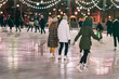 Group of girs skating back to us. Girlfriends ice skating in city park, snowy evening. Healthy outdoor winter activity