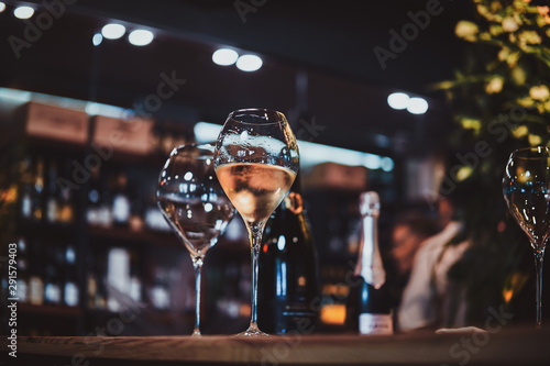 Fotografie, Obraz Wine glasses on the bar table, one glass is empty, but the second one is filled with white wine