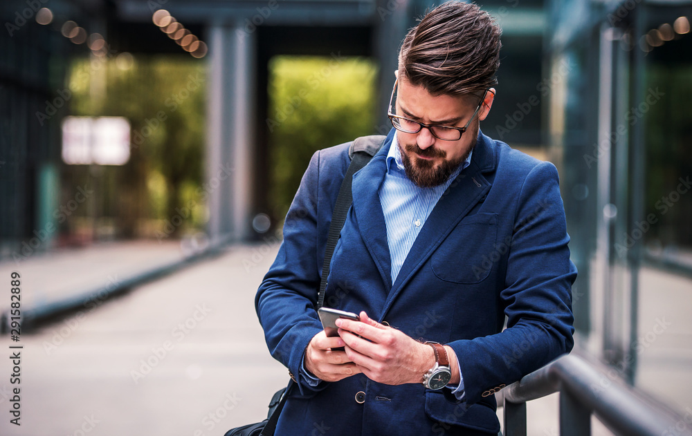 Fototapeta Business man standing in front of the office and using mobile phone. Business, education, lifestyle concept