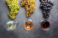 Glasses With White, Red And Pink Wine And Ripe Grapes On Black Stone Background, Top View
