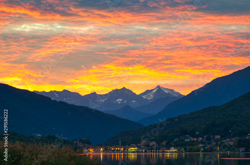 Montage in der Fensternische Rotglühen Traumhafter Sonnenuntergang an einem See mit Bergen im Hintergrund