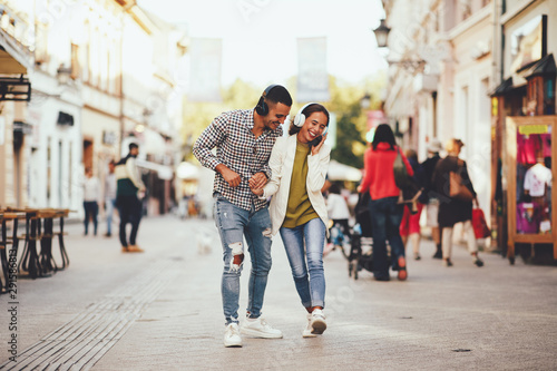 Happy young couple dancing on the street and listening to music through headphon Poster Mural XXL