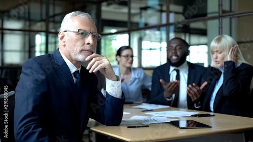 Fotografía Pensive senior businessman thinking, nervous colleagues arguing, stress at work