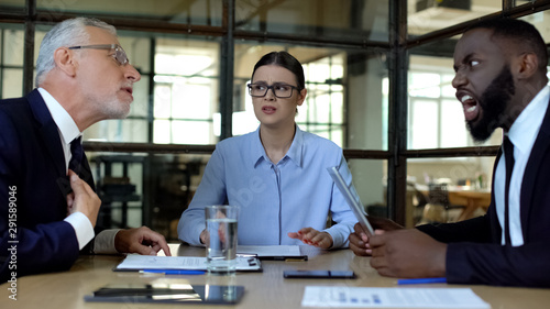 Photo Upset business woman looking at colleagues arguing at office meeting, stress