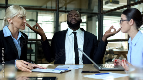 Vászonkép Businessman meditating in office, tired of female colleagues conflict at work