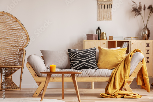 Fotografie, Obraz  Stunning wicker peacock chair next to modern scandinavian settee with pillows