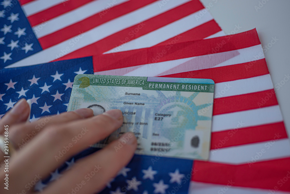 Fototapety, obrazy: Permanent Resident Green card  of United states of America on flag of USA. Above close up view.