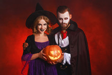 Happy Halloween!  Couple Man And Woman  In A Dracula Vampire And Witch Costumes  With  Pumpkin On  Glowing Red Background.