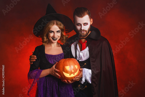 Photo  happy Halloween!  couple man and woman  in a Dracula vampire and witch costumes  with  pumpkin on  glowing red background