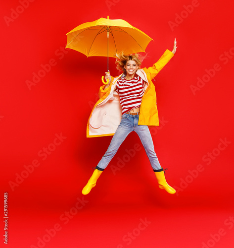 young happy emotional cheerful girl laughing and jumping with yellow umbrella   on colored red background. - 291599685