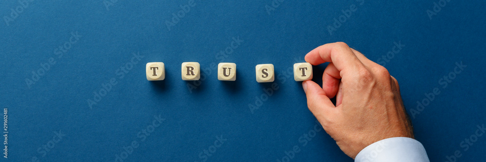 Fototapeta Businessman assembling the word trust with wooden dices