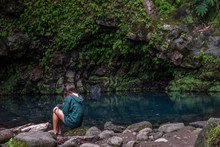 Young Girl Contemplating Poco Azul Waterfall (blue Well) In A Subtropical Forest With Blue Color Pool Surrounded By Green Plants, Achadinha, Nordeste, São Miguel Island, Azores, Portugal
