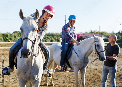Fotomural  Mature couple with trainer riding horse at farm outdoor