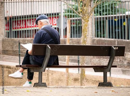 Photo persona mayor jubilada leyendo periódico en el banco del parque
