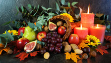 Happy Thanksgiving Cornucopia Table Setting Centerpiece Decorated With Autumn Leaves, Fruit, Nuts And Orange Burning Candles, Close Up.