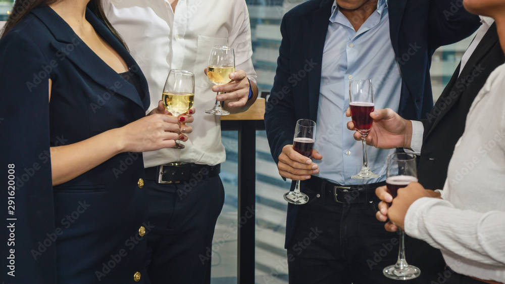 Fototapeta business people with glass of wine and champagne on hands having business discussion in corporate party to celebrate company success