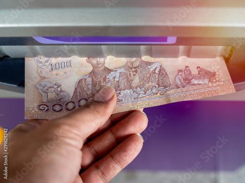 Valokuva Close-up hand withdraw money from ATM machine.