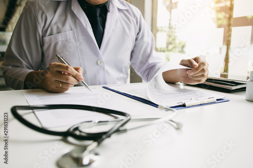 Doctor hand holding pen writing patient history list on note pad and talking to the patient about medication and treatment Wallpaper Mural