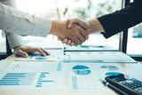Entrepreneurs collaboration deal shaking hands in a modern office and financial paper graph on desk. - 291631422