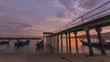 Timelapse Golden hour of sunset at fisherman village with traditional boat parking at the jetty.