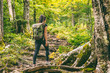 Leinwanddruck Bild - Forest hike trail hiker woman walking in autumn fall nature background in fall season. Hiking active people lifestyle wearing backpack exercising outdoors.