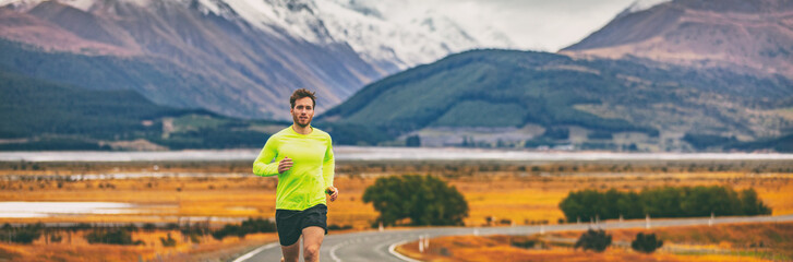Athlete runner running in mountain landscape in panoramic banner background. Man run exercise long distance training outdoor in cold autumn weather.