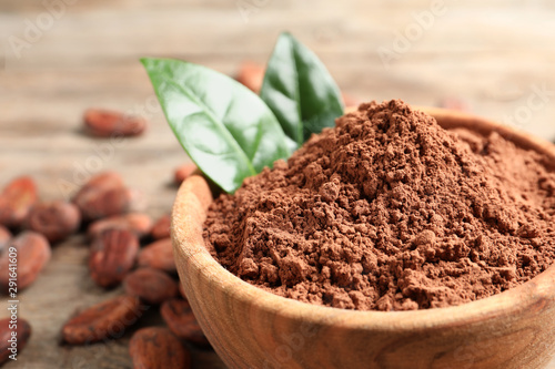 Fotografía  Bowl with cocoa powder on wooden table, closeup. Space for text