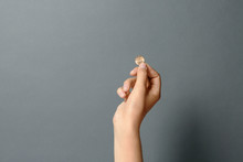 Young Woman Holding Coin On Grey Background, Closeup. Space For Text