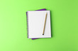 Leinwanddruck Bild - Notebooks with pencil on light green background, top view