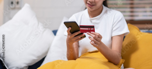 Photo sur Toile Oiseaux sur arbre Young asian woman is holding credit card and using smartphone for online shopping.sitting on sofa.Close up