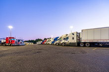 Different Big Rig Semi Trucks With Semi Trailers Standing In Row On Truck Stop Parking Lot At Evening Time For Rest Of Drivers And Safety Requirements For Freight Forwarders