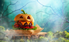 Halloween Party Burger In Shape Of Scary Pumpkin  On  Wooden Board. Halloween Food Concept.