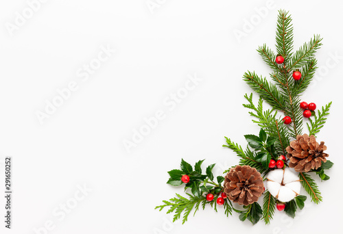 Fotografía  Christmas composition  with branches of spruce and holly with red berries on white background