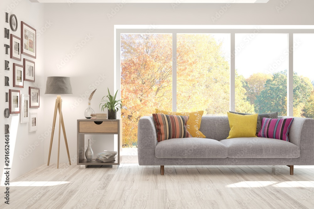 Fototapeta Stylish room in white color with sofa and autumn landscape in window. Scandinavian interior design. 3D illustration