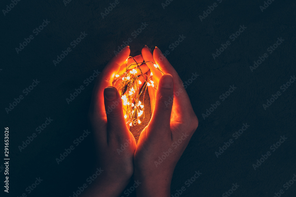 Fototapeta Woman hand holding illuminated garland in her hands in dark