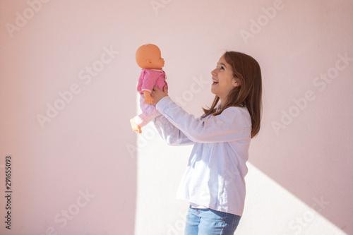 Photo Niña de pie jugando con una muñeca en la azotea