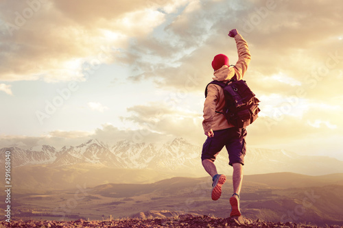Fotomural Happy man jumps in winner pose against sunset mountains