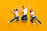 Full length body size view portrait of three nice attractive charming slim sporty cheerful cheery ecstatic person buddy fellow having fun isolated over bright vivid shine yellow background