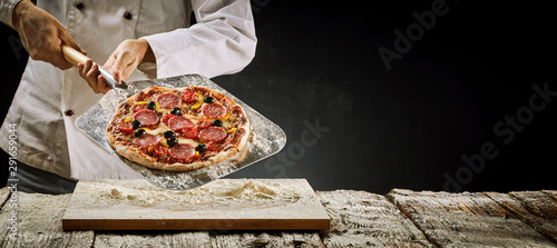Printed kitchen splashbacks Amsterdam Chef removing a salami pizza from the oven