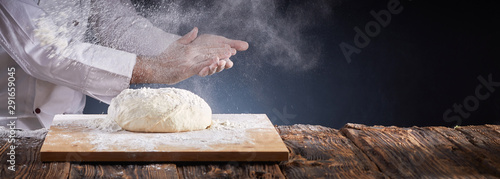 Photo sur Aluminium Boulangerie Chef or baker dusting dough with flour