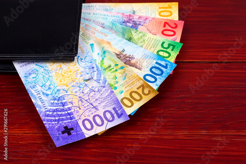 Valokuvatapetti Swiss Francs in the black wallet