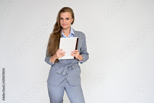 Fotografie, Tablou Portrait of a beautiful manager girl in a gray business suit on a white background with a folder in her hands