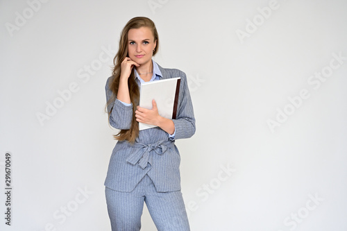 Obraz na plátne  Portrait of a beautiful manager girl in a gray business suit on a white background with a folder in her hands