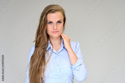 Fototapeta  Close-up portrait of a beautiful manager girl in a gray shirt on a white background