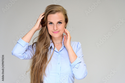 Fotografia, Obraz  Close-up portrait of a beautiful manager girl in a gray shirt on a white background
