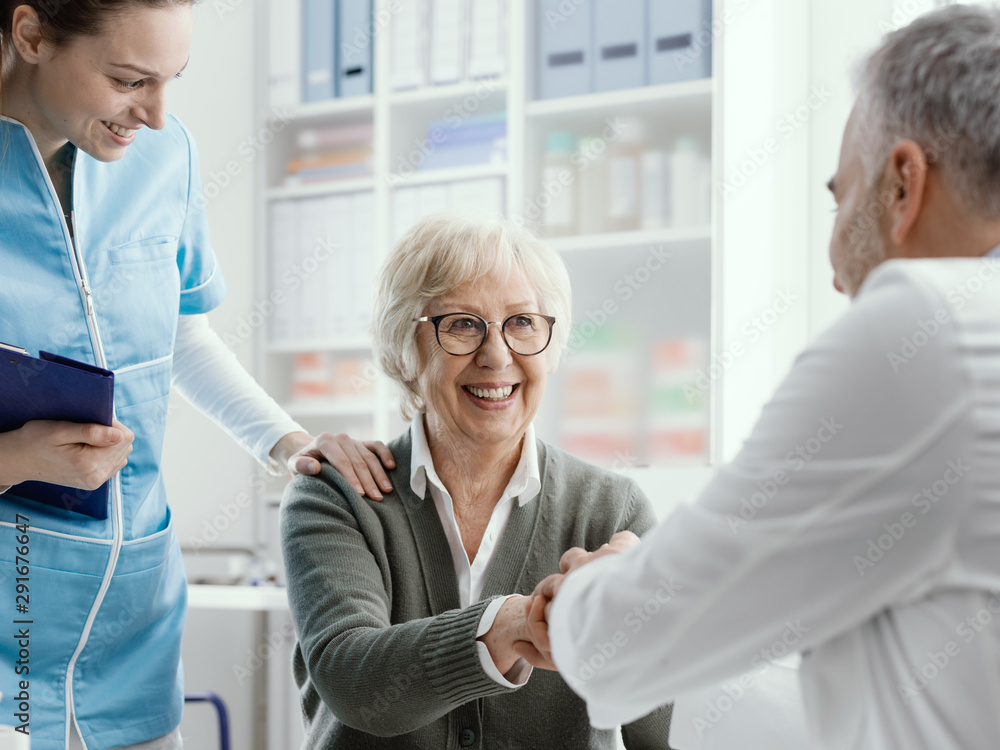 Fototapety, obrazy: Doctor giving an handshake to a senior patient