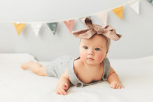 Beautiful Baby Lies On Bed Smiling Bow On Her Head.