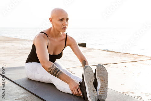 Carta da parati Image of confident bald woman doing exercises on mat while working out