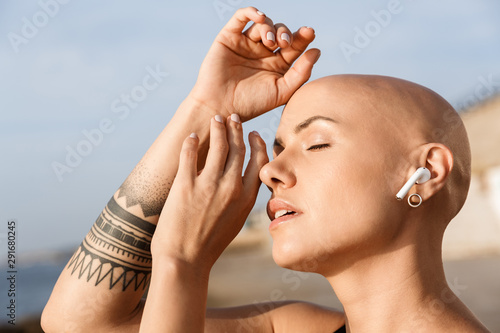 Image closeup of pleased bald woman using earphones with eyes closed - 291680245