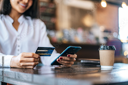 Fototapeta Pay for goods by credit card through a smartphone in a coffee shop. obraz
